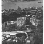 A view from half way up The Peak with a tram ascending the tramway, below is Victoria with to the left center across from the Star Ferry terminal the Hong Kong & Shanghai Bank building.To its right is the open space of the Hong Kong Cricket Club grounds and away further right Causeway Bay and Wanchai. To the right half way down was the Governor's residence. Across the harbor is Kowloon and beyond that the New Territories.