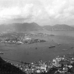 A general view from The Peak looking across Victoria toward Kowloon and the New Territories This was taken in August 1950 and two of the vessels lying at anchor in mid stream are HMS Unicorn (an aircraft carrier) and HMS Ceylon (a cruiser) that were to carry the first contingent of British troops from Hong Kong to Korea to form the 28th Brigade.