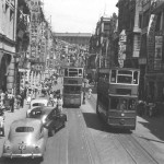This was one of the principal streets in Victoria. See the bustling throngs, all the flags and streamers on the buildings and across the street. The trams were four wheeled. 1st class passengers traveled on the upper deck, everybody else down below. There seemed no limit to the number carried and three conductors were required to keep order and collect fares.