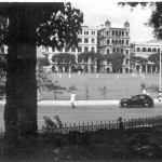 Hong Kong Cricket Club with a match in progress in central Victoria, October 1950. Queens Road runs from left to right. On the other side are the Police HQ, Government offices and further right the RN Dockyard. The photo was taken from the grounds of the Cheero Club.