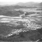 See how the camp site was a little above the level of the paddy fields that stretch to the distance across the valley. Across it runs the railway-the straight line-the winding Shum Chun River and Shung Shui lies toward the center. The border with China is just out of the picture to the left. The scenery is typical of the New Territories. The Guard Room is to the right, the tents the Battery occupied are either side of the track across the site, the officers tents up the valley to the left, and the cookhouse and NAAFI are toward the center in Nissen huts. The site is more compact than I recall.