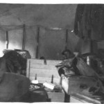 "The interior of our tent of our tent on a wet day. The only ""furniture"" we had were wooden boxes that contain a soldier's gear, to us a ""boxes soldier""; you can see an example center above, along with our hanging uniforms. The tents were difficult to keep tidy in those conditions, and there was not a great deal of comfort. The object in the middle rear is Ian Styles collapsed on his bed."