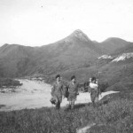 "We are on our way to ""Able' OP with High Junk Peak in background. From the left you see Sergeant Mason with tripod, John Flann with Simms on his back, and I think Frank Beames, with a folding chair round his neck and the radio. Our truck is below at the end of the track."