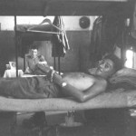 Jock Lyon, in front, is prone on my bunk. Behind him is Ian Styles on his. To the right is my boxes soldier, below are my plate, mug and eating irons next my boots. Above my bunk are uniforms on hangers. The shiny object on the wall behind Ian is his steel helmet. To the left is the open fireplace. A domestic note is the orange box next to Ian with some personal photographs on it belonging to the occupant of the upper bunk. Note the lack of comforts; e.g., a decent mattress, no sheets for the bed (though I think we had them), and no furniture, along with the bare barrack room.